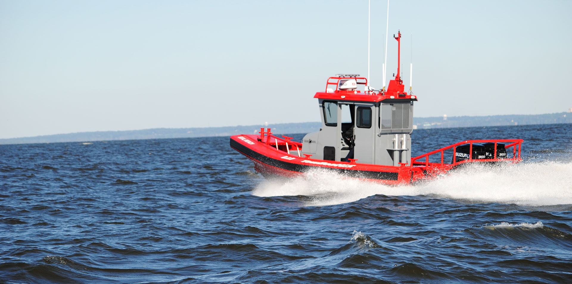 Red and gray Tow Boat U.S. Ambar boat on open ocean